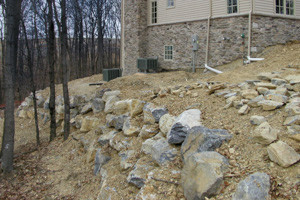 Builder installed boulder embankment on steep slope