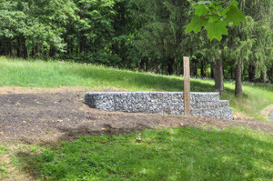 Entry area before with gabion wall and sign feature and meadow in background