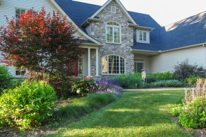 Sweeping lawn path through plantings leads to home entry