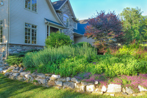 Front yard slope extensive planting bed with client installed boulder retaining wall