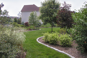 Flowing lawn path and edged bordering screening beds for outdoor living privacy