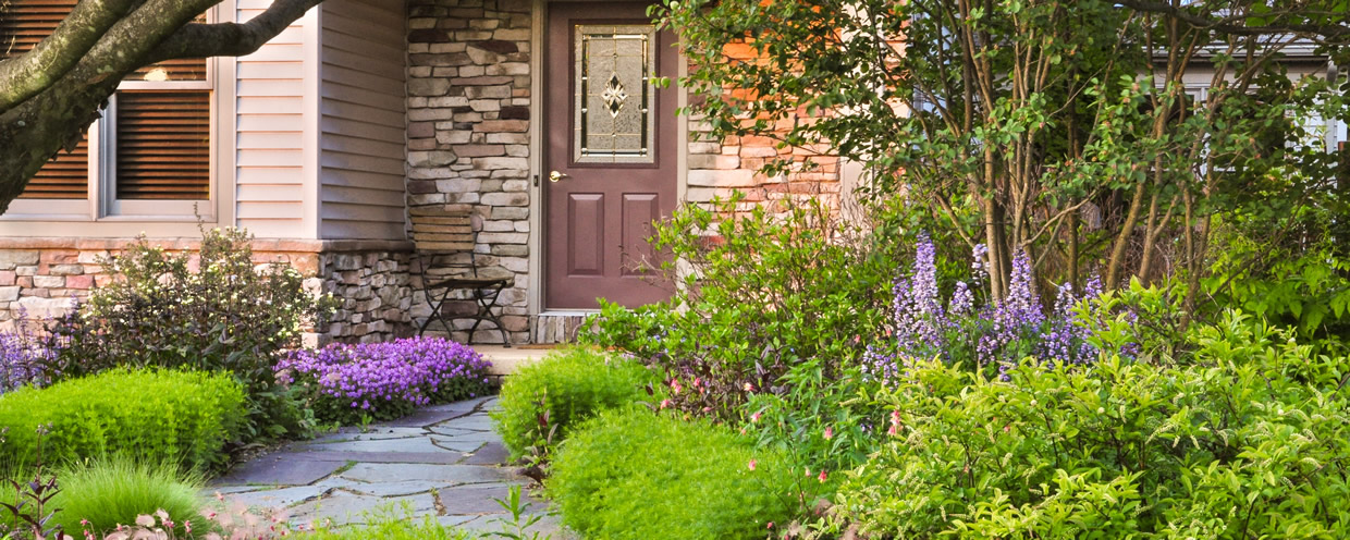 Natural flagstone walk leading to home front porch through natural garden mixed plantings