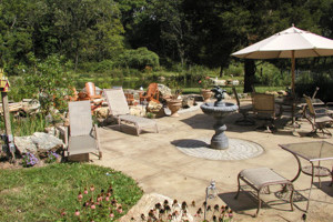 A full featured Outdoor Living Area with patio, furniture, firepit and pond